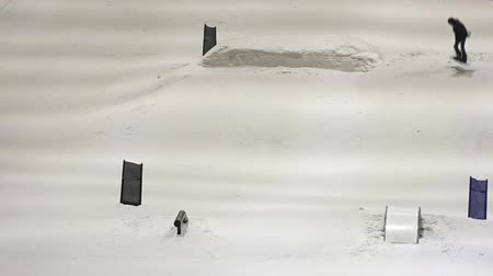 manmade : Man snowboarding in Snow Planet.Its New Zealands first indoor snow facility features 50cm of real snow of a terrain park for freestyle skiers, snowboarders and learners sloop