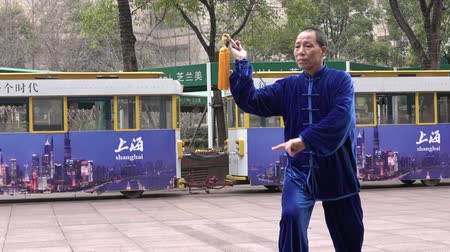 taiji : SHANGHAI, CN - MAR 17 2015:Chinese people practice Tai Chi in Nanjing Road Shanghai China.It is an internal Chinese martial art practised for both its defense training and its health benefits. Stock Footage