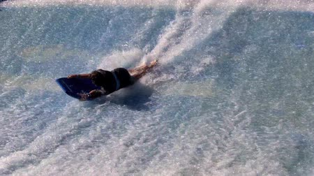 esportivo : GOLD COAST OCT 29 2014: Man ride a surfing board on FlowRider. It is a water park attraction that simulate the riding of waves in the ocean
