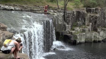waterfall cascading into pool : KERIKERI, NZL - FEB 9 2015:Man jumps off Charlies Rock waterfall in Kerikeri, New Zealand.Kerikeri, the largest town in Northland New Zealand and a popular tourist destination in New Zealand.