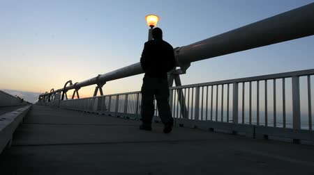 atracação : A man walks over the Gold Coast Pier during sunrise  at the Spit in Queensland Australia.