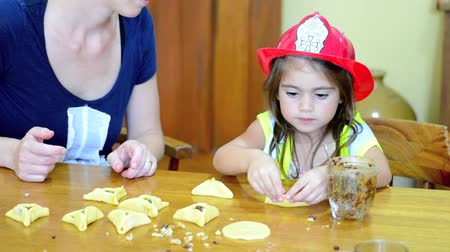 zsidó : Jewish Mother and her child daughter girl age 5 in costume preparing and cooking togather home made Hamantaschen cookie  on Purim Jewish Holiday.