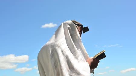 modlitba : Time-lapse video clip of a Jewish man wearing Tallit and Tefillin read from the Torah book pray to God under the open blue sky with sheep clouds.