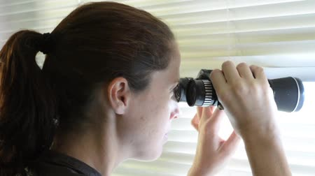 espião : Young woman age 25-30  looks and searches with binoculars and looks out through Venetian blinds. Concept footage of curious, spy, nosy woman.