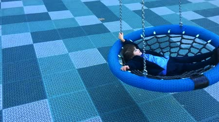 schooler : Slow motion of a happy little girl swings on Birds Nest Swing at the playground Stock Footage