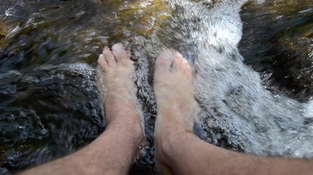 menő : Man wash his legs and foot in cool and fresh spring water. Stock mozgókép