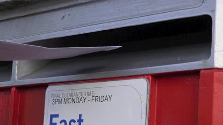 mensagem : Slow motion of person hand posting a letter in a mail letter box