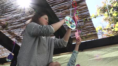 sukkah : Jewish woman and child decorating  their family Sukkah for the Jewish festival of Sukkot. A Sukkah is a temporary structure where meals are taken for the week. Stock Footage