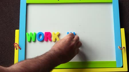 desemprego : Man looking for a job placing advertisement of Work Wanted from letters on a whiteboard. Work concept