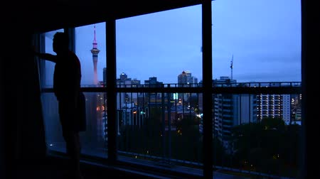 határkő : Man looking out window with aerial urban view of Auckland city skyline at dusk Stock mozgókép