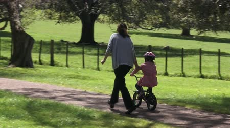 país : Parent Young mother age 30 teaching a child girl age 5-6 how to ride bicycle without stabilizers in the park