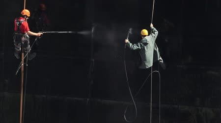 risco : Washers wash the windows of modern skyscraper.Window cleaning is considered one of the most dangerous job in the world.Several window cleaners die each year and many are injured