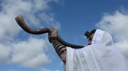 kippur : Jewish man blow Shofar outdoors under the sky, on the Jewish High Holidays in Rosh Hashanah and Yom Kippur Stock Footage