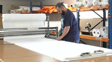 kumaş : Worker cut new fabric sheet for the new National flag of New Zealand. Between 20 Nov and 11 Dec New Zealanders will consider options to their National Flag future