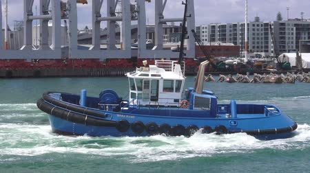 nzl : AUCKLAND,  NZL - JAN 31 2016:Tugboat works at Captain Cook Wharf in Ports of Auckland, New Zealand.Tugboat, small, strongly built vessel, used to guide large oceangoing ships into and out of port