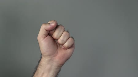кулак : Man hand show fist on a grey background. Concepts and ideas with copy space