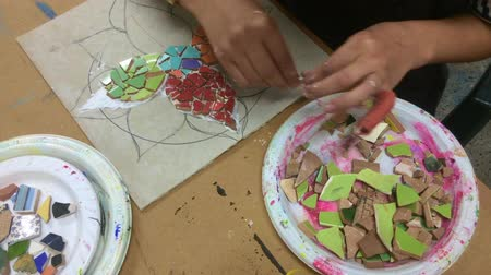 mosaico : Woman hands creating a handmade mosaic artwork at home.