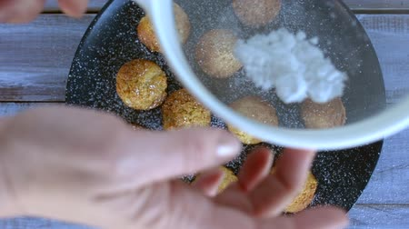 сахар : Woman hands sprinkling icing sugar on mini muffins. Food and cooking concept