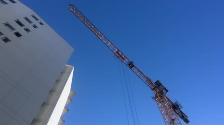fotokopi makinesi : Yellow tower crane at work in construction site.Tilt up camera movement low angle view