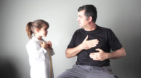 chest pain : Child (girl age 6-7) role playing doctor with dad. Family medical concept. copy space