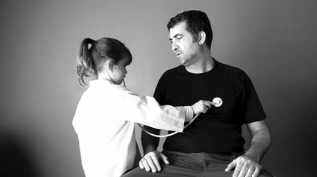 нападение : Child (girl age 6-7) role playing doctor with dad. Family medical concept. copy space