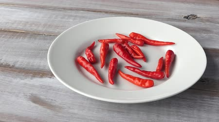 peperoni : Red tiny chilis in a white palte on wooden background. Food background and texture Stock Footage
