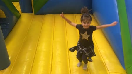 Young girl (age 6) jumps on bouncing castle. Стоковые видеозаписи