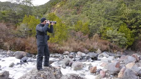birding tours : Professional nature, wildlife and travel photographer photographing outdoors during on location photo assignmet in Tongariro National Park rain forest, New Zealand. copy space.