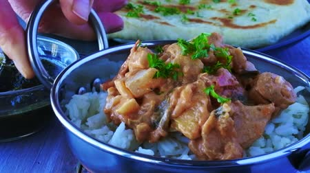 kari : Indian woman serve a traditional Indian butter chicken curry with basmati rice. Food background.