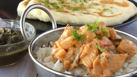 kari : Indian woman serve a traditional Indian butter chicken curry with basmati rice. Food background. 4K