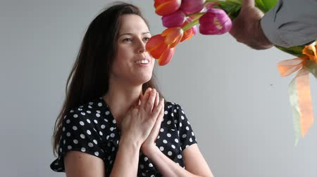receber : Surprised woman (age 30-35) recive tulip flowers from her lover. Couple relationship concept. copy space