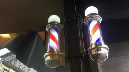 kuaför : American barber pole sign with a helical stripe (red, white, and blue ) on a wall of a Barbers shop.