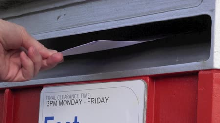 letras : Slow motion of person hand posting a letter in a mail letter box
