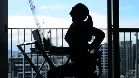 arka görünüm : Side view Silhouette of Young woman (age 30-40) having back pain while working at desk in office. Woman work healthcare lifestyle concept. Real people. copy space Stok Video