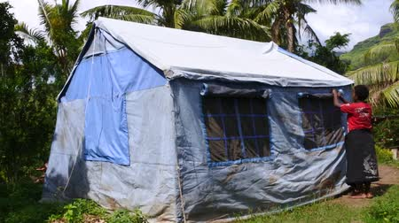 unicef : Victim of Cyclone Winston live in UNICEF tent in Navala village. Fiji struggles to rebuild a year after Cyclone Winston tropical storm devastated the country on February 2016. Stock Footage