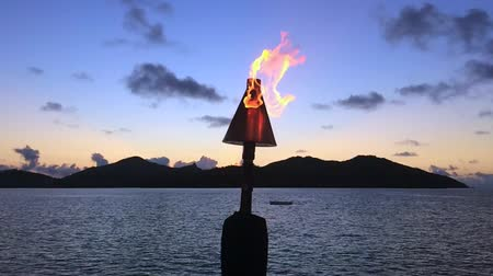 fiji : Slow motion of a Torch Fire Flame in a resort, against tropical island landscape in the Pacific Islands.
