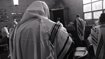 tallit : Jewish men praying in synagogue.Jewish men are obligated to conduct tefillah (prayer) three times a day within specific time ranges in the morning, afternoon and evening.