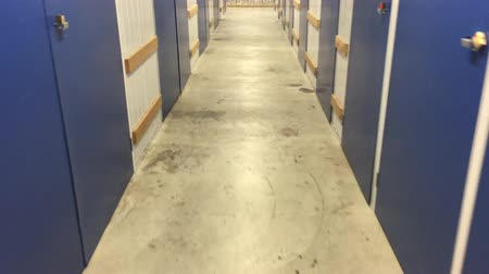self storage : POV of person walks through unrecognizable industrial self storage place full of doors. Stock Footage