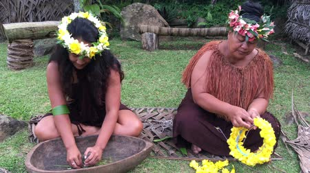 koszorú : Two Pacific Islander women works outdoor in a Maori village in the highlands of Rarotonga, Cook Islands.