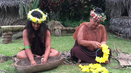 cook islanders : Two Pacific Islander women works outdoor in a Maori village in the highlands of Rarotonga, Cook Islands.