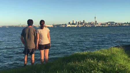 félteke : Time lapse of couple looks at Auckland city skyline New Zealand at sunset Stock mozgókép