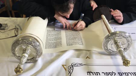 geçen : Jewish man holding Sofer hand while he writing a sefer Torah in Hebrew. In the Torahs 613 commandments, the second to last is that every Jew should write a Sefer Torah in their lifetime.
