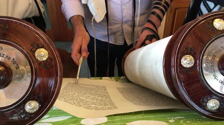 holy book : Jewish men praying from the Torah together. Reading the Torah is one of the bases for Jewish life.