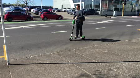 car rental : Young man riding on Lime electric scooters.The scooters have a 48km maximum range. Users find, unlock and pay for them using an app and leave them at their destination.
