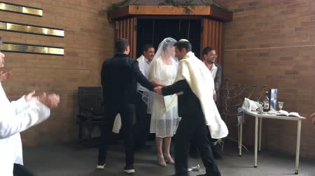 Happy Jewish bride and bridegroom dancing in a Orthodox Jewish wedding ceremony in a synagogue.Jewish wedding is a wedding ceremony that follows Jewish laws and traditions Stock mozgókép