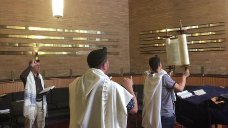 tallit : Jewish man carrying a Torah scroll in a synagogue. Reading the Torah is one of the bases for Jewish life.