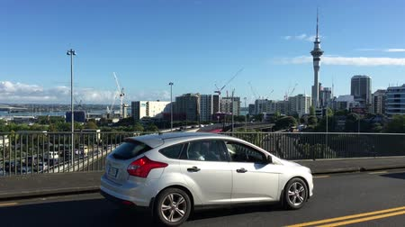Pedestrians and vehicles traffic against Auckland city downtown. Auckland is the financial center of New Zealand