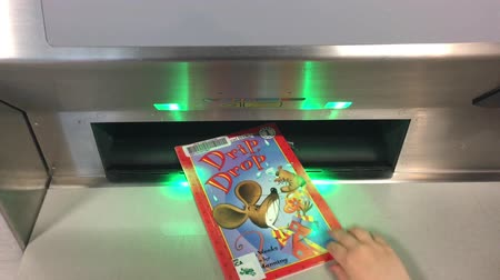 Hand of a child returning a book into an automated book return machine.Students who do more reading at home are better readers and have higher math scores