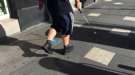 Unrecognizable blind man using white cane. Primarily it aids its user to scan their surroundings for obstacles or orientation marks and  identifying the user as blind or visually impaired.