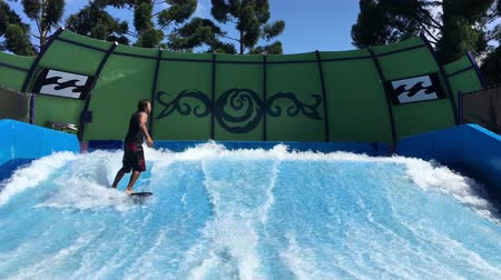 Young man flowriding and flowboarding on artificial sheet waves. The water flows up and over surfaces engineered to replicate the shape of ocean waves.